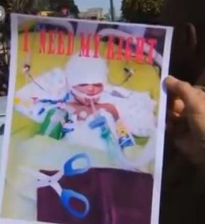 Διαδηλωτές κρατούν αφίσα με το παιδί και τα ψαλίδια