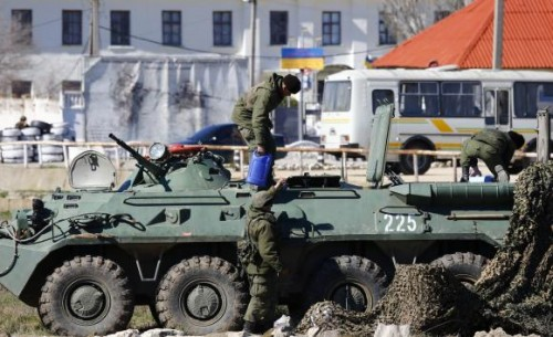 Armed men, believed to be Russian servicemen, supply an armoured personnel carrier (APC) in front of a Ukrainian marine base in the Crimean port city of Feodosia
